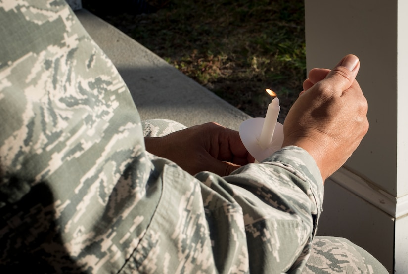 Col. Jimmy Canlas, 437th Airlift Wing commander, holds a lit candle during a moment of silence remembering all of those affected by domestic violence during a ceremony at Joint Base Charleston, S.C., Oct. 30, 2017.