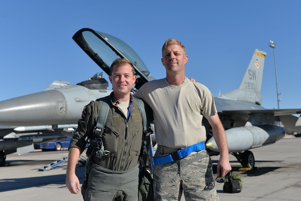 "U.S. Air Force 1st Lt. Brian Davis, 55th Fighter Squadron F-16CM Fighting Falcon pilot, left, and Senior Master Sgt. Daniel Henderson, 20th Aircraft Maintenance Squadron, 55th Aircraft Maintenance Unit, ""Shooters"" assistant superintendent, stand next to each other in front of jet 830 for a photo prior to takeoff at Nellis Air Force Base (AFB), Nevada, Oct. 10, 2017."