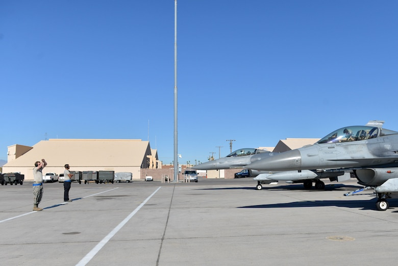 Tactical aircraft maintainers prepare to marshal out F-16CM Fighting Falcons at Nellis Air Force Base (AFB), Nevada, Oct. 10, 2017.