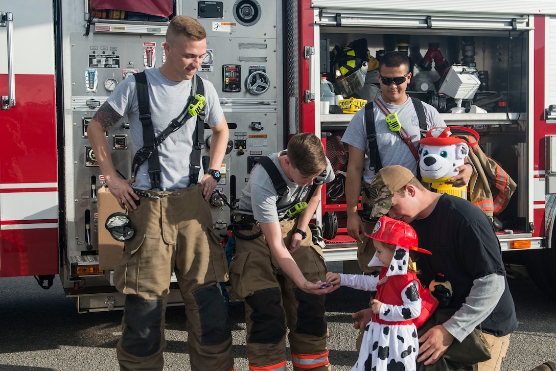 U.S. Airmen assigned to the 20th Civil Engineer Squadron fire department hand out candy to a Team Shaw child at Shaw Air Force Base, South Carolina, Oct. 28, 2017.