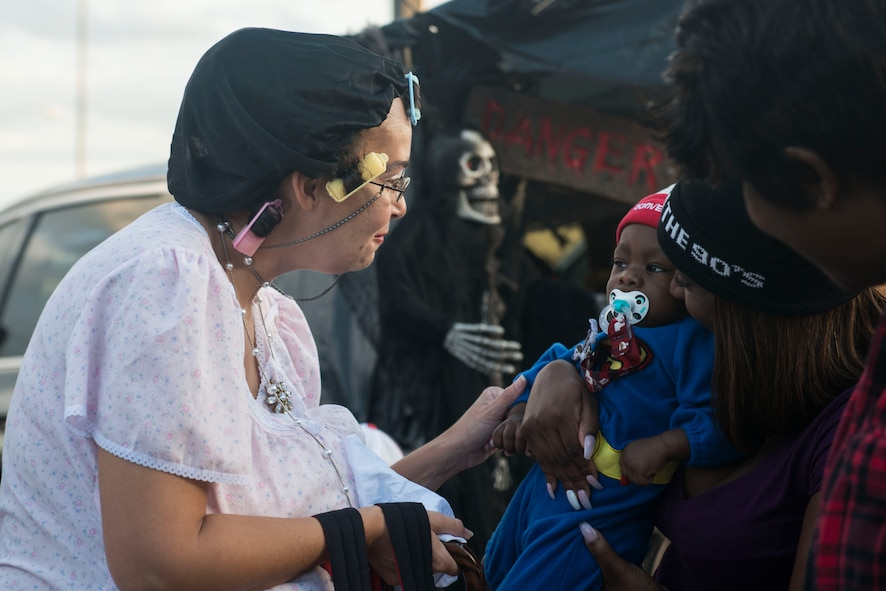 """A Team Shaw member interacts with a child during the """"trunk-or-treat"""" portion of the annual Boo Bash at Shaw Air Force Base, South Carolina, Oct. 28, 2017."""
