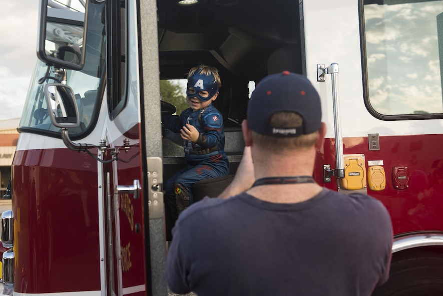 A Team Shaw member takes a picture of a child sitting in a firetruck during the ninth annual Boo Bash at Shaw Air Force Base, South Carolina, Oct. 28, 2017.