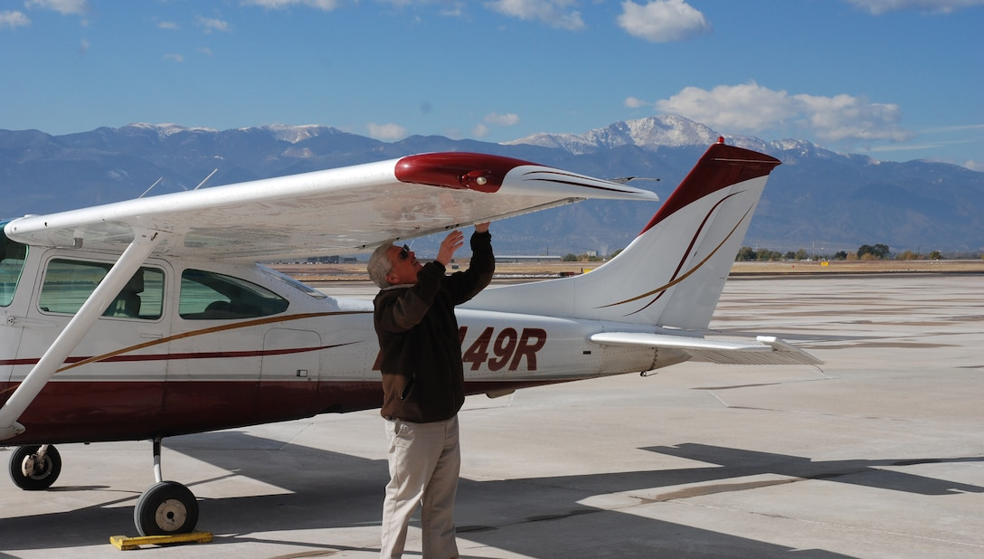 Greg Cortum, Peterson Air Force Base Aero Club/Rocky Mountain Flight Training Center manager, undertakes a preflight walk around at the club hangar on Peterson Air Force Base, Colorado on Oct. 31, 2017. The group was recognized as a 2017 Aircraft Owners and Pilots Association Training Experience Awards Distinguished Flight School. (U.S. Air Force photo by Dave Smith)