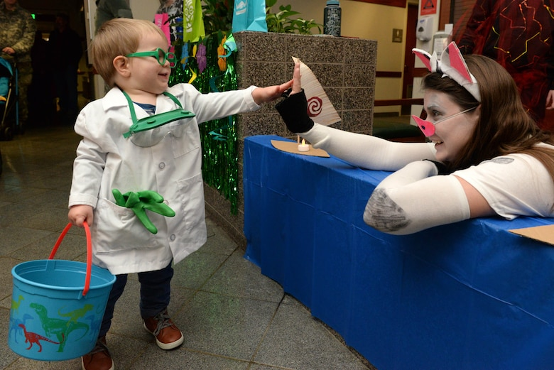 David, son of Tech. Sgt. John Jenkins, non-commissioned officer in charge, weather specialty teams, greets the 673d Medical Support Squadron Women's Health Clinic staff member at the annual 673d Medical Group trick-or-treat event at Joint Base Elmendorf-Richardson, Alaska, Oct. 27, 2017. During this event the hospital will transform the clinic lobbies into themed stages for costumed hospital staff to pass out candy to participants on Oct. 26, 2018.