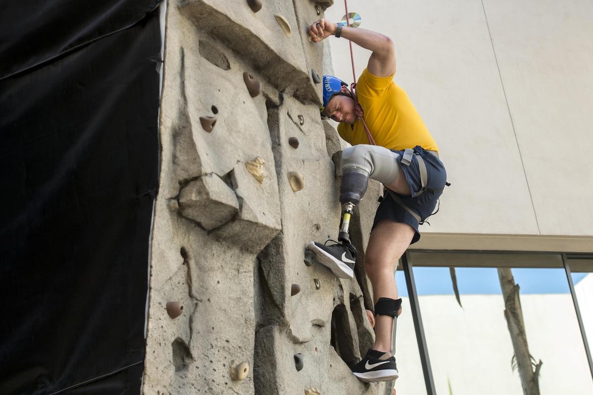 A service member scales a rock climbing wall.