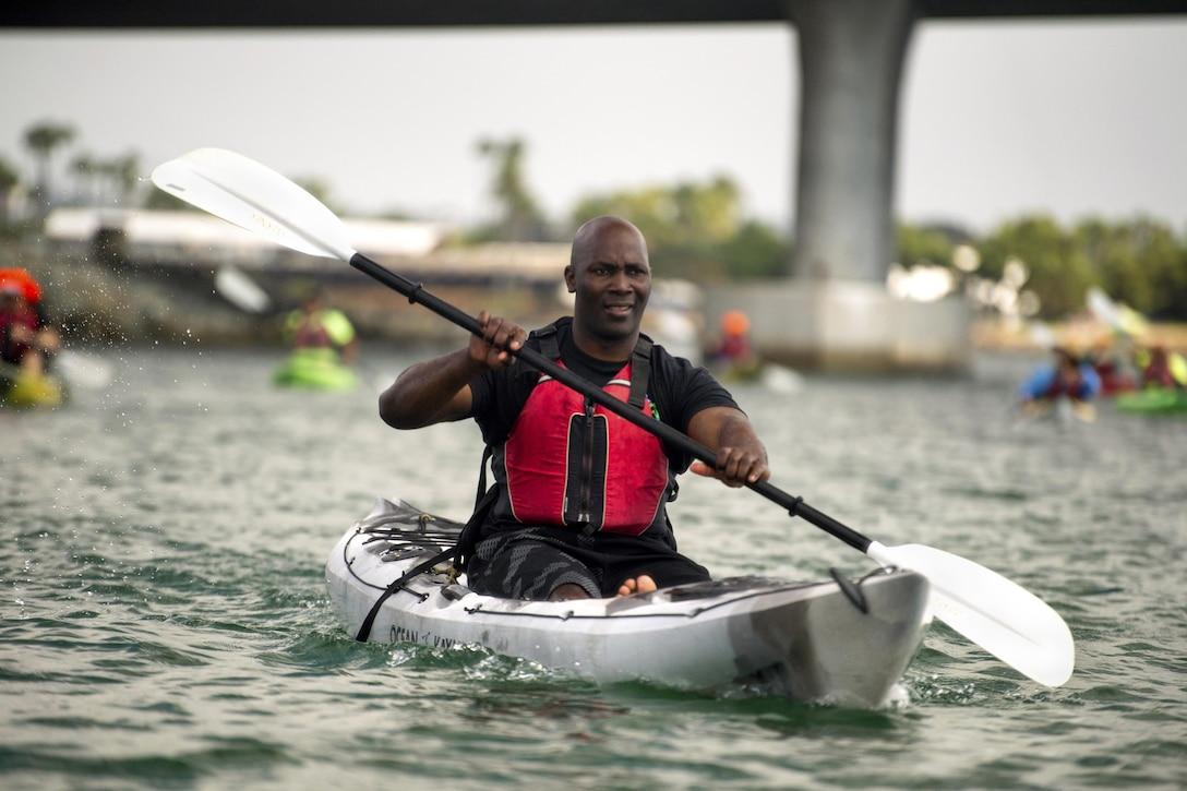 A service member paddles along a bay in a kayak.