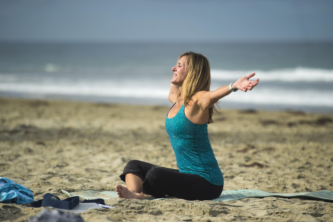A yoga instructor extends her arms while in a seated position.
