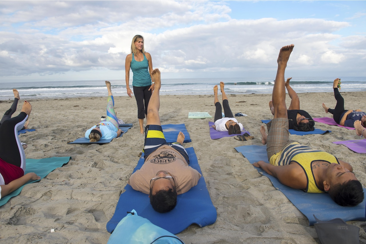 An instructor stands while a group of yoga participants lay on the beach with one leg up.