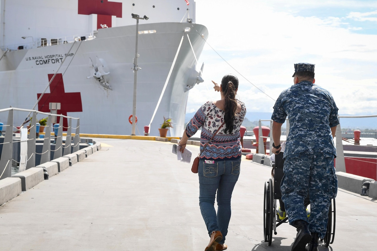 A sailor pushes a wheelchair and walks with a person to a ship.