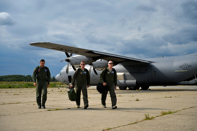 U.S. Air Force C-130J pilots from the 37th Airlift Squadron, (right and center), along with one Romanian Air Force pilot, walk back to their units after conducting a training flight at Otopeni Air Base, Romania, Aug. 29, 2017.