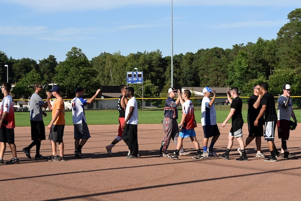 Players from opposing teams high-five one another to show good sportsmanship at the end of an intramural softball game Aug 22, 2017, on Ramstein Air Base, Germany. Professionalism and sportsmanship are two key factors of the intramural sports system that help to boost morale. (U.S. Air Force photo/Airman 1st Class Milton Jr. Hamilton)
