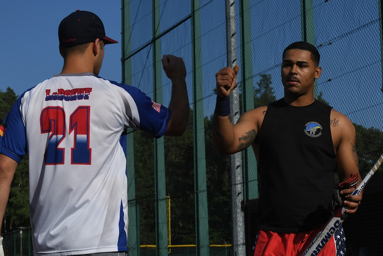 U.S. Air Force Airman 1st Class Kristopher Cooper, 86th Maintenance Squadron sheet metal technician, bumps fists with a teammate to celebrate a good inning during an intramural softball game on Ramstein Air Base, Germany, Aug 22, 2017. Cooper's team went on to win the championship game, ending their season with 10 wins and two losses. (U.S. Air Force photo by Staff Sgt. Nesha Humes Stanton)