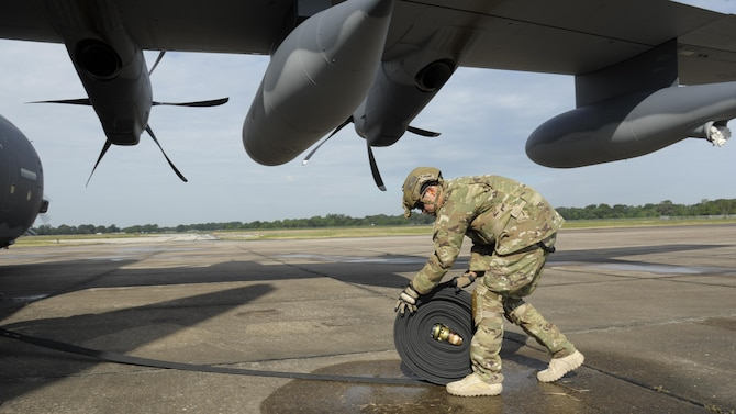 U. S. Air Force Staff Sgt. John San Inocencio, 23d Logistics Readiness Squadron, rolls a fuel line toward a HC-130J Combat King II Aug. 31, 2017, following a hot refuel of a MH-60S Seahawk at Jack Brooks Regional Airport in Beaumont, Texas.