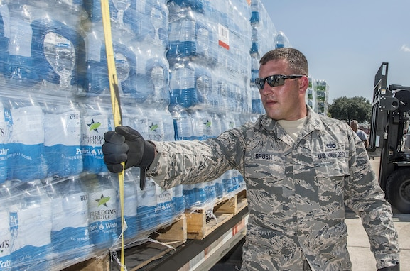 Soldier in fatigues secures pallet of water with tie-down strap, facing viewer's half-left.