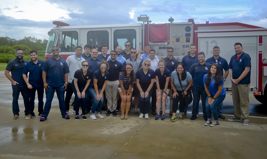 Tampa Bay Rays Staff pause for a photo in front of a fire truck during a tour at MacDill Air Force Base, Fla., Aug. 28, 2017. The Tampa Bay Rays Staff visited several locations including the fire station, military working dogs and the air traffic control tower. (U.S. Air Force photo by Senior Airman Mariette Adams)