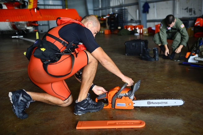 A Coast Guardsman starts a chainsaw on the floor of a command center.