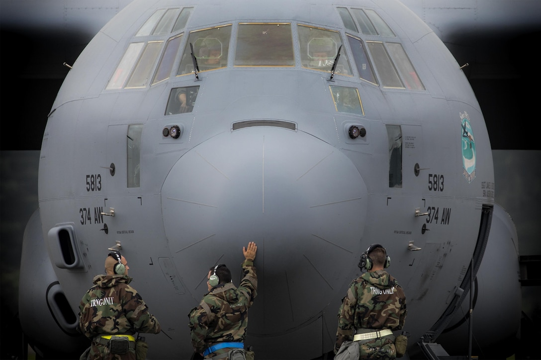 Crew chiefs from the 374th Aircraft Maintenance Squadron await a C-130J Super Hercules engine to start during Exercise Beverly Morning 17-05 at Yokota Air Base, Japan, Aug. 18, 2017. The training is designed to test the ability of Airmen to survive in austere environments with chemical, biological, radiological, nuclear and explosive hazards. (U.S. Air Force photo/Yasuo Osakabe)