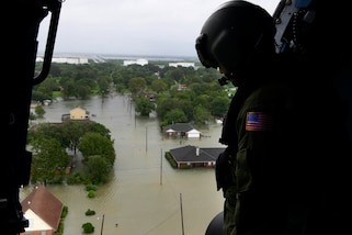 A Coast Guardsman peers out of the door of an aircraft flying over flooded streets.