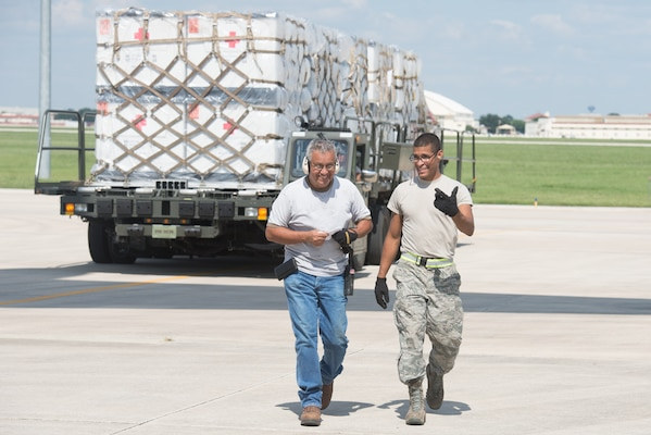 Members from the 502nd Logistics Readiness Squadron and the 433rd Airlift Wing load pallets containing medical supplies and equipment