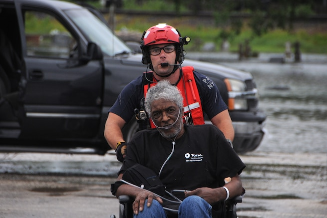 A guardsman pushes an elderly man toward with flooded streets behind them.