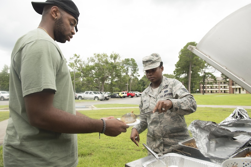 Staff Sgt. Torri Reed, right, 628th Air Base Wing chaplain assistant, serves food to Airman 1st Class Jakorey Johnson, left, 437th Maintenance Squadron crew chief, during a dinner for dormitory residents hosted by The First Sergeants Council and Joint Base Charleston Chaplains Office in the courtyard outside the dorms Aug. 30, 2017.