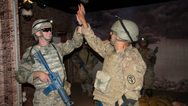 Tech. Sgt. Joshua B. Welter, 621st Contingency Response Squadron aircraft maintenance craftsman, and U.S. Army Sgt. Christopher A. Kilby, animal care specialist and NCO in charge of Joint Base McGuire-Dix-Lakehurst Veterinary Treatment Facility, high five each other after completing a portion of training at the Medical Simulations Training Center at Joint Base McGuire-Dix-Lakehurst, N.J. on Aug. 17, 2017. The MSTC provides training to all branches of the military, federal, and local law enforcement and fire agencies. (U.S. Air Force photo by Airman 1st Class Jessica Blair)