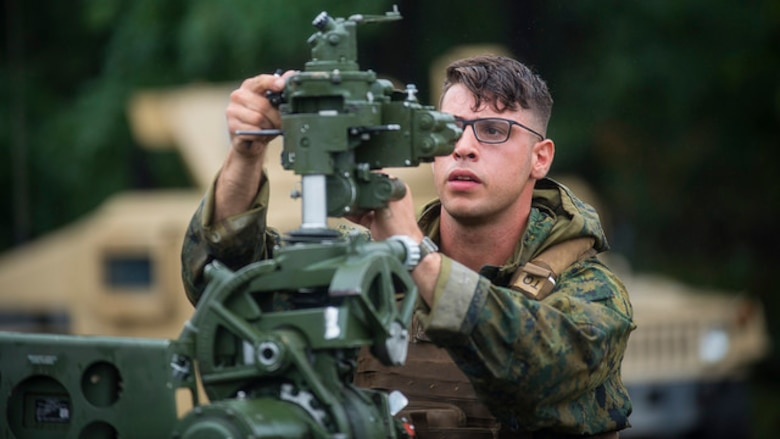 U.S. Marine Sgt. John C. Vassiliou, Battery G, 3rd Battalion 14th Marines field artillery cannoneer, ensures the M777A2 howitzer is leveled properly during artillery training at Joint Base McGuire-Dix-Lakehurst, N.J. on Aug. 18, 2017. The M777A2 is normally operated by a crew of eight but can be operated with a reduced detachment of five. (U.S. Air Force photo by Airman 1st Class Jessica Blair)