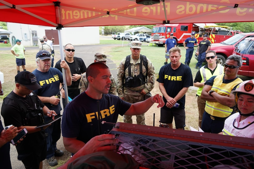A Kauai County firefighter briefs first responders on the simulated hazmat conditions found during Kauai County Exercise 2017 at the Pacific Missile Range Facility in Kauai, Hawaii, Aug. 30, 2017. Hawaii Air National Guard photo by Tech. Sgt. Andrew Jackson