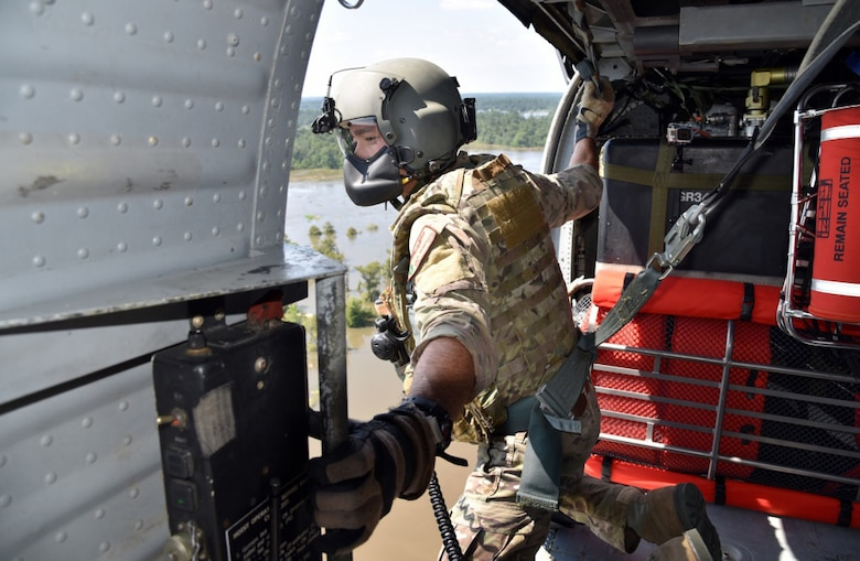 Senior Airman Davy Brinkmann, 920th Rescue Wing, Patrick Air Force Base, Florida, special missions aviations specialist, gets sight on a fellow pararescuemen below as they prepare to hoist two stranded victims of Hurricane Harvey Aug. 31, 2017 from Beaumont, Texas. The 920th RQW deployed roughly 90 Citizen Airmen, three Pave Hawks and two HC-130Ns in support of Air Force Northern's search and rescue mission for FEMA disaster relief efforts. (U.S. Air Force photo/Tech. Sgt. Lindsey Maurice)