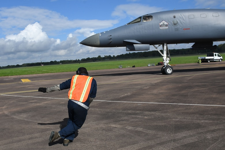 U.S. Air Force Staff Sgt. Ryan Branch, a 489th Bomb Group crew chief, marshals a B-1 Lancer to the taxiway at RAF Fairford, U.K., Aug. 31, 2017.