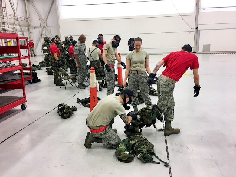 Senior Airman Danielle Monroe (center), emergency management journeyman in the 419th Civil Engineer Squadron, guides Airmen through the survival gear removal process