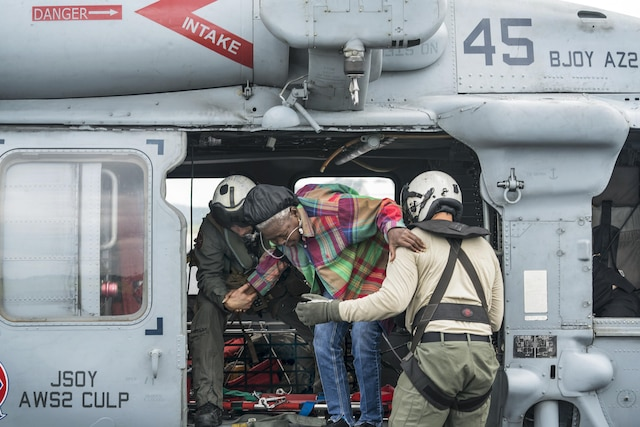 Two Airmen help a civilian woman climb out of an aircraft.