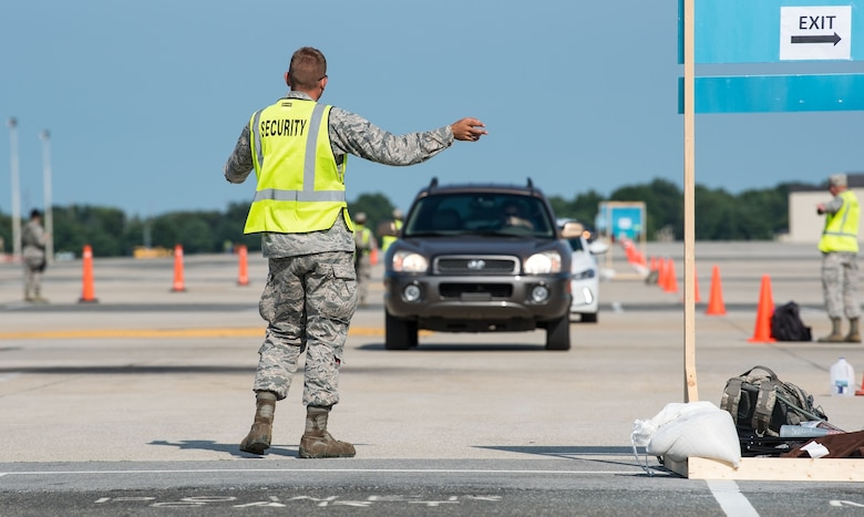"A ""Thunder Over Dover"" volunteer directs incoming traffic from the North Gate to parking on the flight line Aug. 27, 2017, on Dover Air Force Base, Del. This year's Open House showcased the capabilities of our Air Force aviation team and celebrated our longstanding relationship with our neighbors in the local Dover community. (U.S. Air Force photo by Roland Balik)"