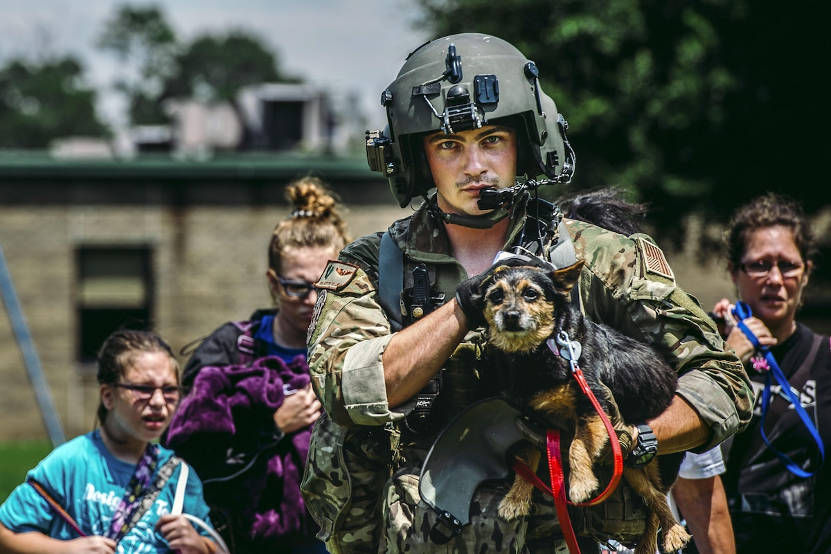 An airman carries a dog and walks in front of family following him.