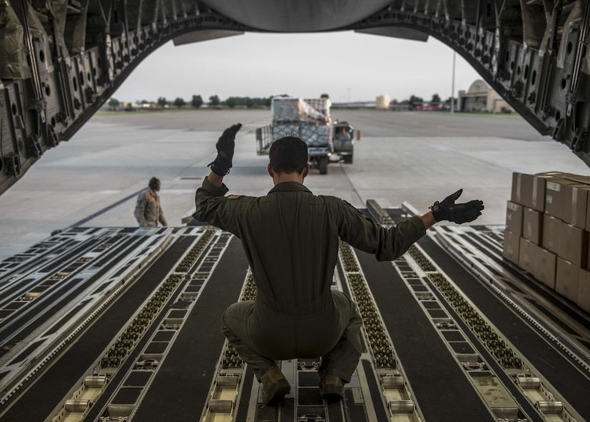A loadmaster with the 6th Airlift Squadron directs 375th Logistics Readiness Squadron personnel toward a C-17 Globemaster III, which will transport cargo and 375th Aeromedical Evacuation Squadron personnel to Little Rock Air Force Base, Ark. to provide medical relief after Hurricane Harvey caused catastrophic floods in the states of Texas and Louisiana, Scott Air Force Base, Ill., Aug. 30, 2017.  The 375th LRS loaded 6.5 tons of medical supplies onto a C-17 Globemaster III for the nine-person medical team. The 375th AES crew, prepared to provide relief for 30 days, will be staged at Little Rock Air Force Base, where they will pick up high-priority patients from George Bush Intercontinental Airport and transport them to one of seven hospital locations across the states of Texas, Oklahoma, Louisiana, Tennessee, Mississippi, and Alabama.   (U.S. Air Force photo by Tech. Sgt. Jodi Martinez)