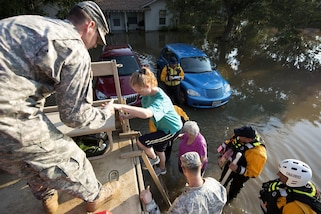 Service members help people into a military vehicle.