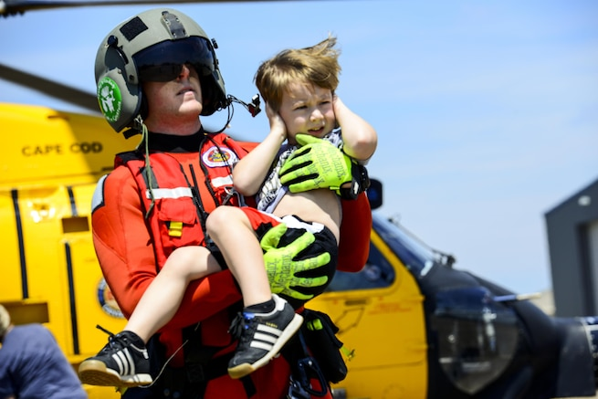 A boy covers his ears as a Coast Guardsman carries him away from a helicopter.