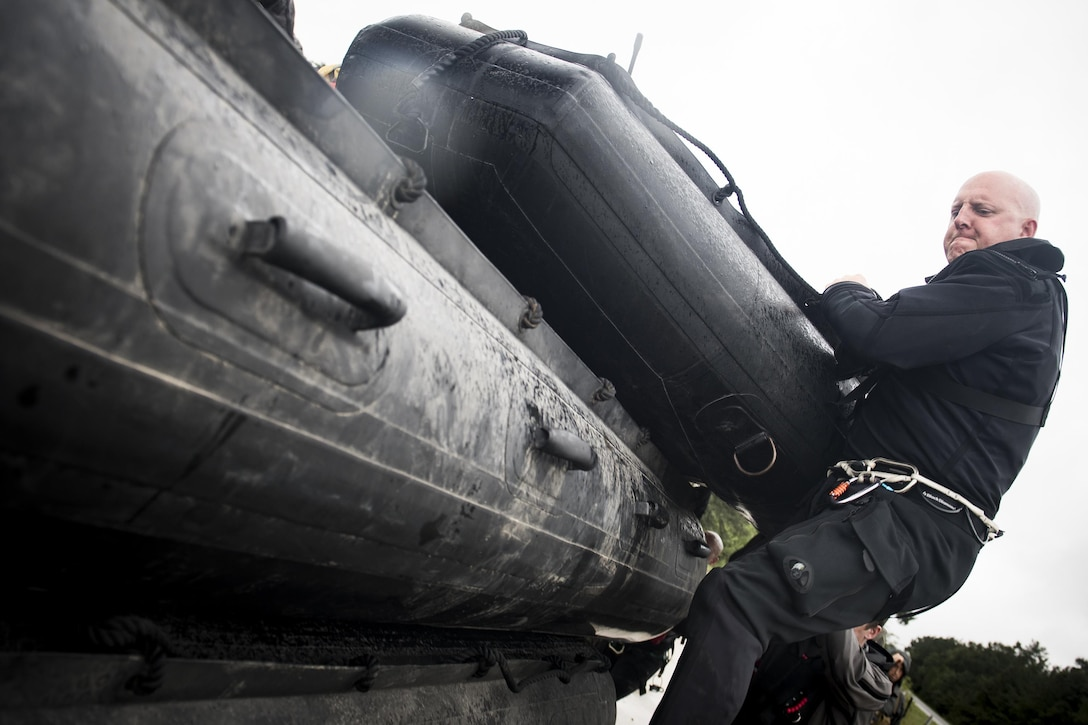 A pararescueman from the 58th Rescue Squadron pushes a stack of rescue boats onto a transport vehicle prior to a rescue mission, Aug. 30, 2017, at the Orange County Convention and Expo Center in Orange, Texas.