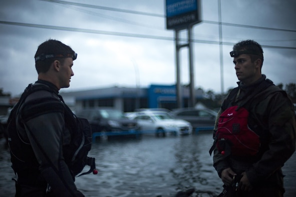 Pararescuemen from the 58th Rescue Squadron strategize outside of a flooded car dealership in Orange, Texas, Aug. 30, 2017.