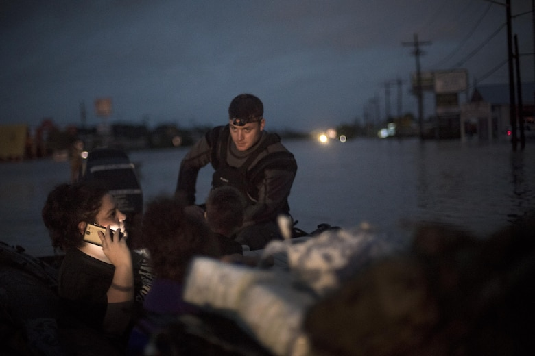 A pararescueman from the 58th Rescue Squadron sits in a rescue boat with a family that was displaced by floodwaters, Aug. 30, 2017, in Orange, Texas.