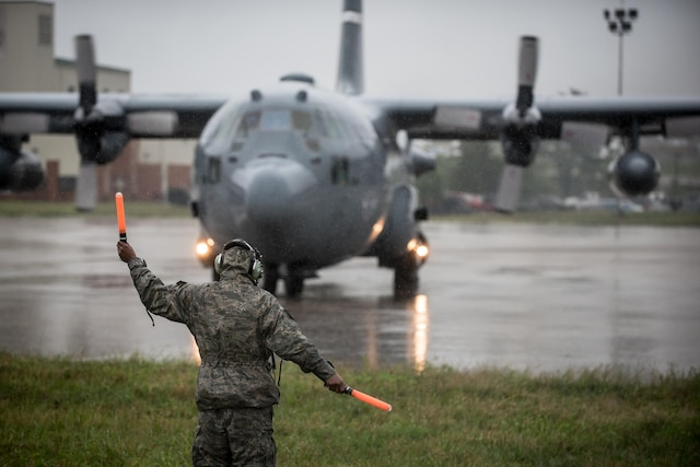 An Airman directs a large aircraft carrying aid for flood victims