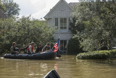 Marines with Charlie Company, 4th Reconnaissance Battalion, 4th Marine Division, Marine Forces Reserve, along with a member of the Texas Highway Patrol and Texas State Guard, patrol past a flooded house in Houston, Aug. 31, 2017. Marine Corps photo by Lance Cpl. Niles Lee