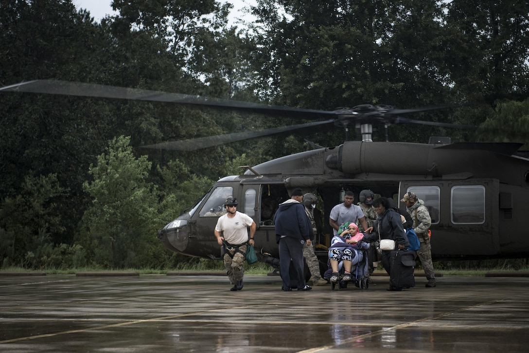 Airmen and Soldiers assist victims out of a UH-60 Black Hawk, Aug. 30, 2017, at the Orange County Convention and Expo Center in Orange, Texas.