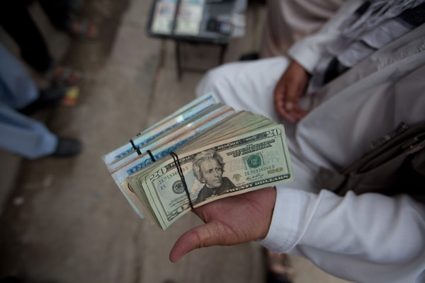 Widespread corruption has permeated the highest levels of the Government of the Islamic Republic of Afghanistan.  Money changer displaying his wares.
