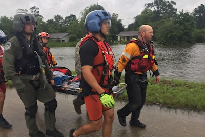 Texas National Guard soldiers and members of the Coast Guard, Texas Task Force 1 and Austin-Travis County Emergency Medical Service swift-water rescue technicians work together to rescue a man with special medical needs from high-rising waters and evacuate him to a safe location in Orange, Texas, Aug.t 30, 2017. Texas Army National Guard photo by Capt. Martha Nigrelle