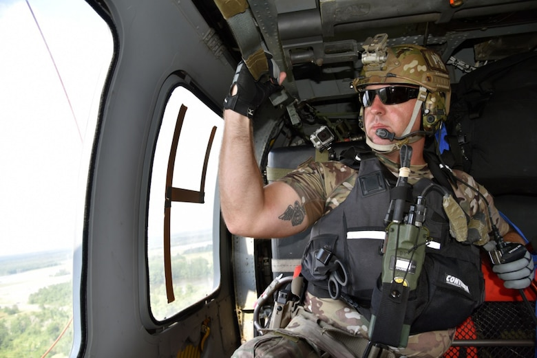 Master Sgt. Brandon Daugherty, 920th Rescue Wing pararescueman, keeps a watchful eye for Hurricane Harvey disaster victims while aboard an HH-60 Pave Hawk helicopter Aug. 31, 2017 in Beaumont, Texas. The 920th Rescue Wing, deployed roughly 90 Citizen Airmen, three Pave Hawks and two HC-130Ns in support of Air Force Northern's search and rescue mission for FEMA disaster relief efforts. (U.S. Air Force photo/Tech. Sgt. Lindsey Maurice)