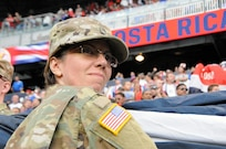 Master Sgt. Chanda Caro, assigned to the U.S. Army Reserve's 99th Regional Support Command, headquartered at Joint Base McGuire-Dix-Lakehurst, New Jersey, helps hold the flag Sept. 1 prior to the start of a United States men's national soccer team game at Red Bull Arena in Harrison, New Jersey.  Service members from the Army and Air Force held the U.S. flag for the national anthem.