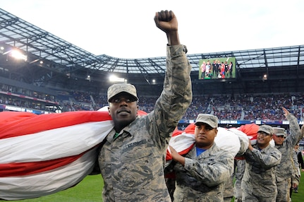 Airmen 1st Class Ezell Jones Jr., assigned to the U.S. Air Force's 305th Maintenance Squadron, reacts to the crowd Sept. 1 after helping to hold the U.S. flag for the national anthem.  The service members were there to hold the flag for the national anthem as part of a military appreciation theme for the game.