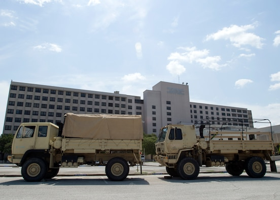Two light medium tactical vehicle is parked outside of the old Wilford Hall Ambulatory Surgical Center Sept. 2 after dropping off 67 soldiers, on Joint Base San Antonio-Lackland, Texas. More than 500 soldiers are awaiting future deployment instructions at the old Wilford Hall in response to the devastation caused by Hurricane Harvey. (U.S. Air Force photo/Staff Sgt. Kevin Iinuma)