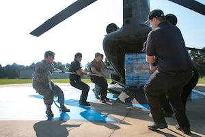Soldiers unload pallets of water from a helicopter.